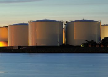 Photo of oil and gas storage tanks at dusk